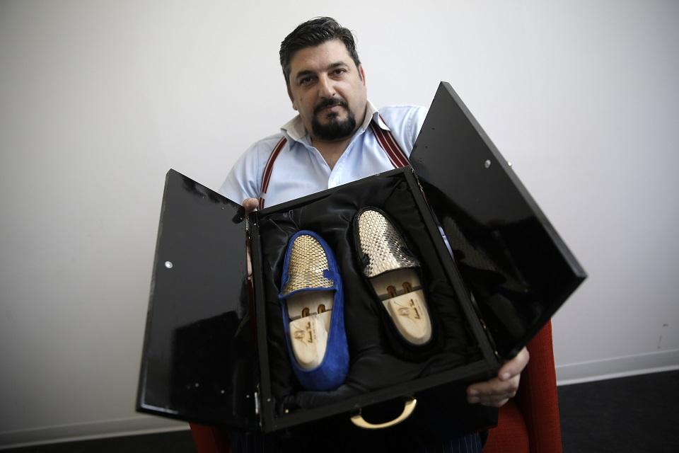 Italian shoe master sews shoes in gold